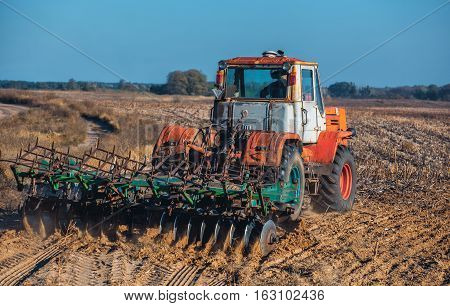 Large old beautiful tractor plowing the earth on the field after harvest autumn harvest sunflowers. Employment of agricultural equipment and machines.