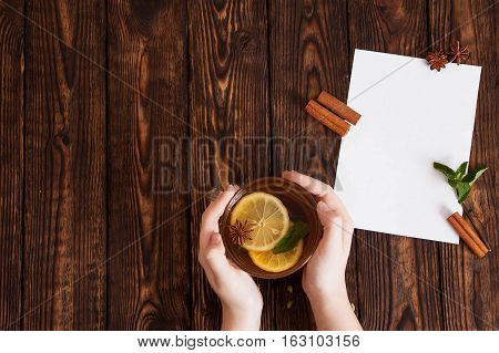 hands holding a mug with tea and lemon at the table