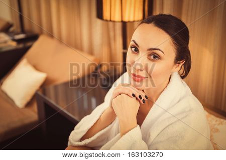 Peaceful girl is relaxing at beauty salon in aroma therapy room. She is sitting in white bathrobe. Lady is smiling and looking at camera with happiness