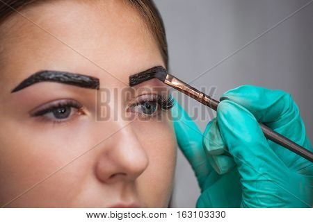 beautician- makeup artist applies paint henna on previously plucked design trimmed eyebrows in a beauty salon in the session correction. Professional care for face.