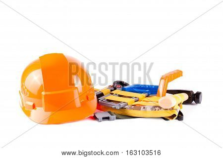 Toy construction helmet and tools over a white background. Children toy tools