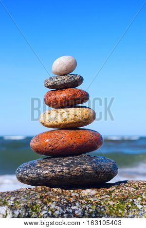 beautiful pyramid of colorful wet pebbles . Rock Zen in the background of the sea. Concept of harmony and balance.