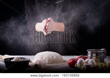 Baker prepares the dough on table. Female hand clap a flour. Concept of baking and patisserie.