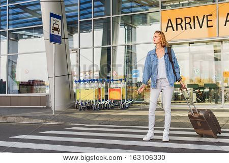 Concerned young girl is waiting for taxi near airport. She is standing on road with luggage and looking aside with anticipation