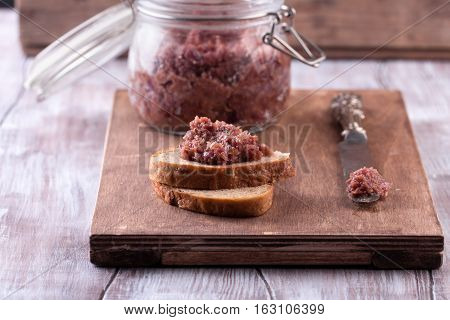 Red onion chutney in a glass jar and toasts with chutney on old wooden cutting board. Rustic table-knife.