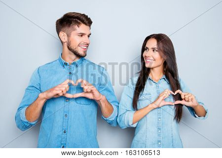 Portrait of happy cheerful man and woman in love gesturing heart