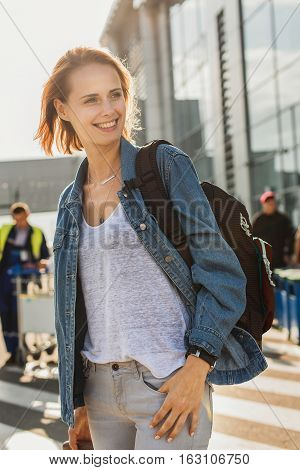 Joyful female tourist is happy to see new city. She is standing outdoors and smiling