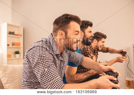 Side View Of Three Friends Playing Video Games At Home