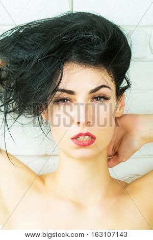 pretty passionate woman or cute girl with sexy body and bare shoulders has long brunette hair and red lips on white brick wall background