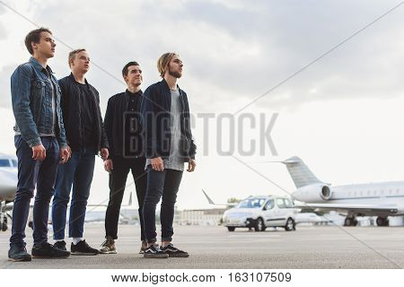 Four young male rock band is standing on airfield and looking up with hope