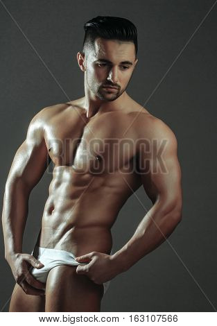 Handsome man or muscular macho bodybuilder with sexy muscle torso body with six packs and abs poses on grey background in white panties poster