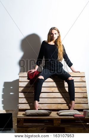 Pretty girl or beautiful woman cute sexy fashion model with long hair in casual clothes sits on backrest of wooden pallet sofa on white wall