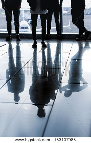 Close up of male legs. Four friends are standing near window at airport hall. Focus on their shadows on floor