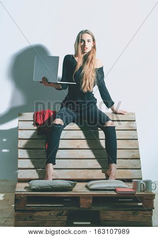 Pretty girl or beautiful woman cute sexy fashion model with long hair in casual clothes with laptop computer sits on backrest of wooden pallet sofa on white wall