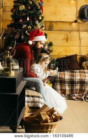 christmas father and daughter in red santa claus hat and sweater writting in book at xmas decorated tree. bearded man with cute girl child at new year holidays celebration near basket with wood