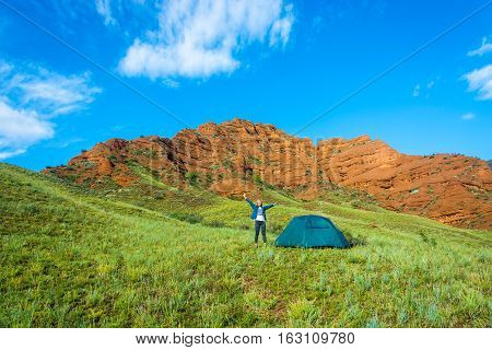 Woman Near Blue Tent On A Background Of Orange Mountains, Kyrgyzstan.