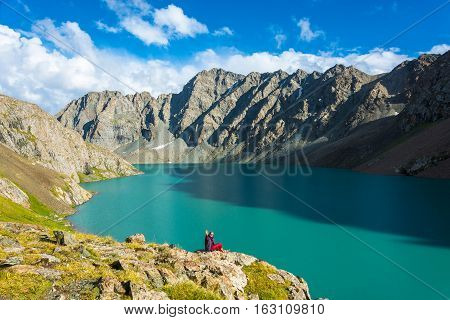 A Woman Sits On The Shore Of A Mountain Lake Ala-kul, Kyrgyzstan.
