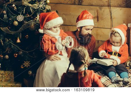 christmas father and children in red santa claus hat and sweater writing and reading book at xmas decorated tree. bearded man with cute kids at new year holidays celebration on wood background