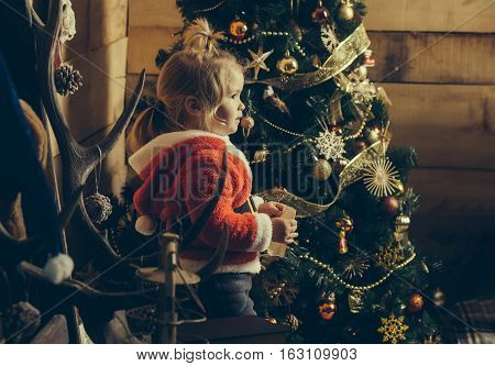 christmas small boy in red santa claus hat and coat reading from paper sheet at xmas decorated tree. cute kid at new year holidays celebration on wooden background