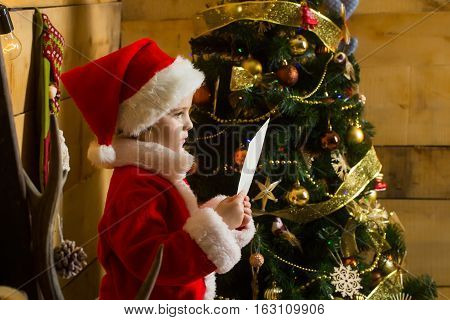 christmas small girl in red santa claus hat and coat reading from paper sheet at xmas decorated tree. cute kid at new year holidays celebration on wooden background