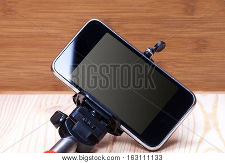 Monopod and phone on wood desk. Gadgetry on board.
