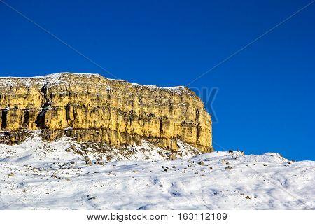 mountain rocks, snow slope, winter landscape, blue sky, nature of the Caucasus