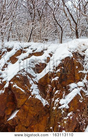 Wisconsin red granite rock and woods with December snow.