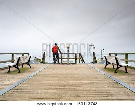 Tourist with red backpack on wooden pier above sea. Man in trekking suit in harbor in dark rainy day. Touristic mole wet wooden floor above sea.