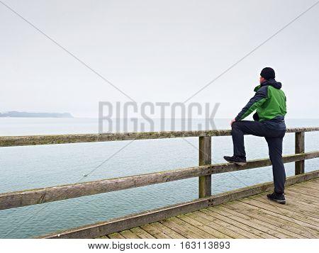 Man Thinking. Tourist  In Green On Sea Mole At Handrail. Autumn Mist