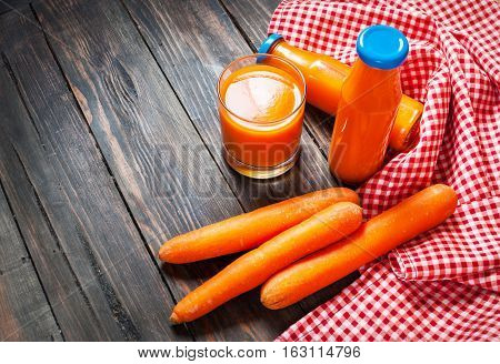 Carrot juice in glass and vegetables beside.