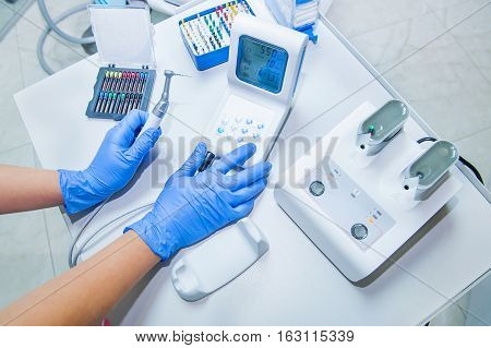 Assistant's Hands Configures Dental Equipment In Dentist's Office. Close Up, Selective Focus. Dentis