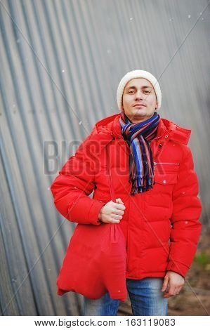 Young handsome man in red jacket standing around a metal fence with a bag of groceries in their supermarket.