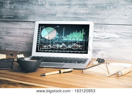 Close up of modern workplace with forex chart on laptop screen coffee cup and supplies. Trade concept