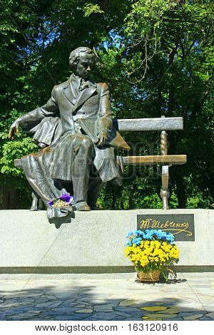 Shevchenko T. monument in Chernihiv with bouquet of yellow and blue chrysanthemum