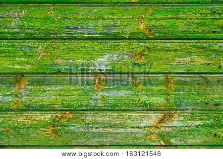 Bright green wooden background. The texture of the wood and peeling of old paint. Vintage Board closeup