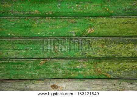 Background texture of old wooden wall. Vintage wood surface is naturally aged. Peeling green paint. Grunge background