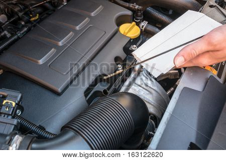 Oil level check in a modern car engine by verifying the dipstick