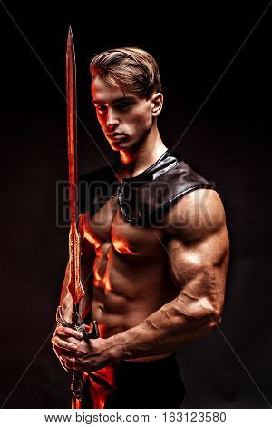 Portrait of sexy muscular man holding sword and looking at camera .