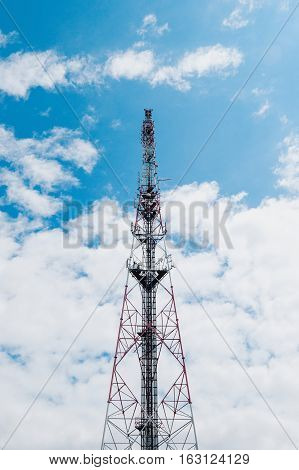 Telecommunication mast with GSM UMTS TV DAB Satellite military antennas wireless technology against cloudy blue sky