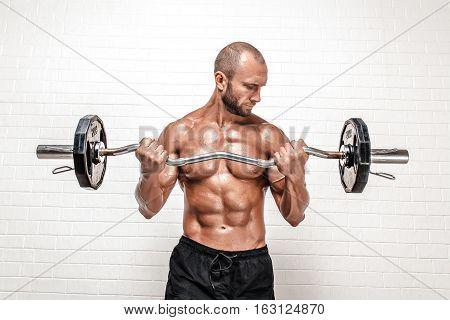 Studio portrait of handsome topless bodybuilder doing exercise on biceps against white background.