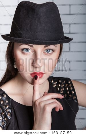Close-up portrait of young woman in hat with finger on lips gestures silently quiet shhh secret facial expression human emotions signs and symbols
