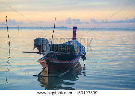 longtail boat standing near the shore at sunrise