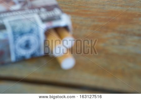 Out of focus pack of cigarettes on wooden table.