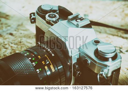 Old camera on wooden plate retouching vintage