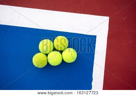 Old five tennis balls on tennis court
