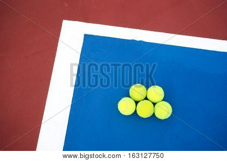Old five tennis balls on tennis court.