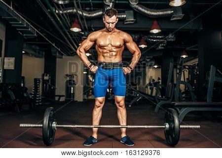 Strong Bodybuilder preparing for deadlift of barbell in the gym,