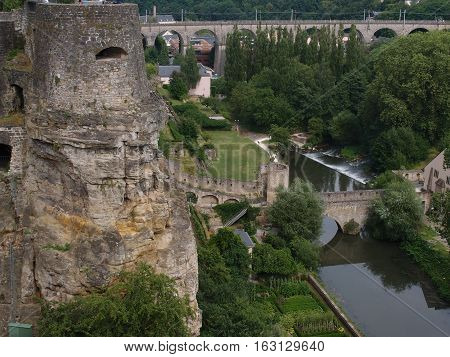 A lookout post for the ancient fortress in Luxembourg City with stone bridges crossing the river on a summer day.