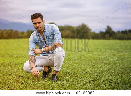 Handsome young man at countryside, in front of field or grassland, wearing shirt, looking at camera