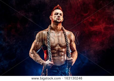 strong athletic man with naked body in military pants and rope on neck dark with red smoke background